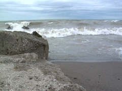 Turbulant waves crash against rocks and rolling up on the shore- slo mo 01 - stock footage