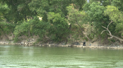 Fisherman on the riverside in the rain throws the fishing rod Stock Footage