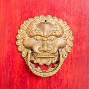 ancient red doors with gilded studs and lion head door knockers - stock photo