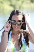 young caucasian woman outdoors sunglasses bikini top - stock photo