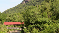Red covered bridge rocky river mountains Stock Footage
