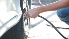 woman checking pressure and inflating car tire. - stock footage