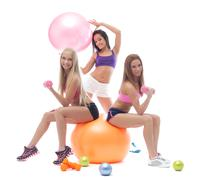 Smiling sporty girls posing with fitness items Stock Photos