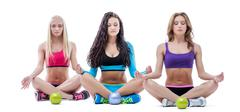Stock Photo of Three relaxed girls meditating in lotus position
