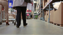 Two persons walking between shop shelves with shopping cart - stock footage