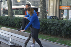 People stretching on street bench, slow motion shot at 240fps, steadycam shot Stock Footage