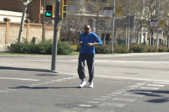 Man jogging and crossing road, slow motion shot at 240fps, steadycam shot Stock Footage