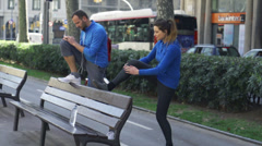 People stretching on street bench, slow motion shot at 60fps, steadycam shot Stock Footage