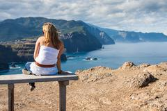 Woman sitting on a bench overlooking oregon coast and cannon beach - late aft Stock Photos