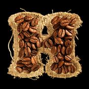 Alphabet from coffee beans on fabric texture isolated on black Stock Photos