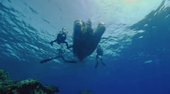 Rubber boat and scuba divers, under water view Stock Footage