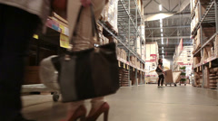 Camera moving along storehouse shelves and people searching goods Stock Footage