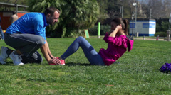 Woman doing sit-ups in park, slow motion shot at 240fps, steadycam shot Stock Footage