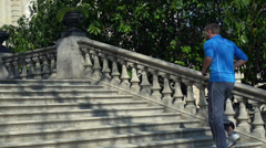 Jogger running up on stairs, slow motion shot at 240fps, steadycam shot Stock Footage