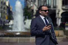businessman walking near fountain and listening music, slow motion shot 240fps - stock footage