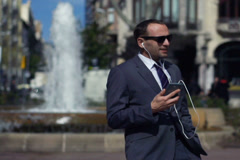 businessman singing and listening music in front of fountain, slow motion - stock footage