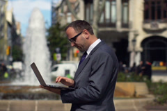 Businessman working on laptop close to the fountain, slow motion shot at 60fps Stock Footage