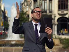 Happy businessman with tablet standing in the street, slow motion shot at 240fps Stock Footage