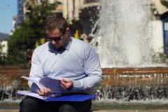 Businessman checking documents by fountain, slow motion shot at 240fps Stock Footage