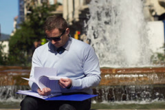 Businessman checking documents and sitting by fountain, slow motion Stock Footage