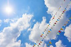 Blue sky with multi colored party flags hanging Stock Photos