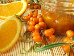 Jam with fruits of sea buckthorn and oranges - stock photo