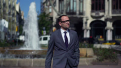 Businessman standing in front of the fountain in the city, slow motion Stock Footage