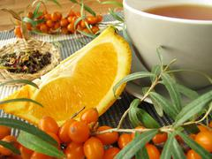 Tea with fruits of sea buckthorn and oranges Stock Photos