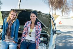 Car defect two women waiting for help - stock photo