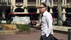 Businessman holding his jakcet and walking along the street on a sunny day Stock Footage