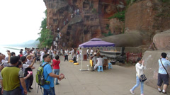 Believers climb down the steep and narrow  stair and gather at the Giant Buddha Stock Footage