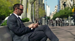 Businessman using his cellphone on a bench in a city, slow motion shot at 60fps Stock Footage