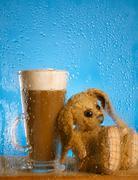 Bunny and coffee latte behind rainy window, shallow dof on glass Stock Photos