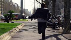 Businessman running to work along the street, slow motion shot at 240fps Stock Footage