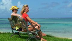 Love couple seat on bench on shore and look at the sea water Stock Footage