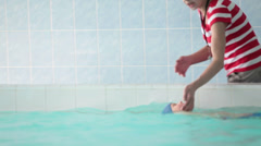 Trainer holding child who swimming on back with board Stock Footage