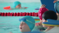 Children in rubber caps and with swim board standing in swimming pool Stock Footage