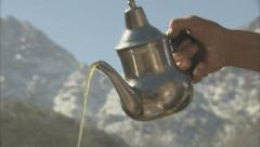 Pouring a traditional glass of mint tea - stock footage