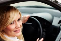 Smiling woman driver at wheel of car Stock Photos