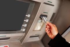 Woman using an ATM Kuvituskuvat