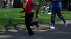 People jogging in park, slow motion shot at 120fps, steadycam shot Stock Footage
