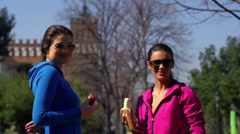 Women eating fruits in park and smiling to camera, slow motion shot at 240fps Stock Footage