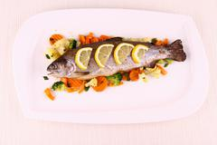 Grilled whole trout with vegetables and lemon Stock Photos