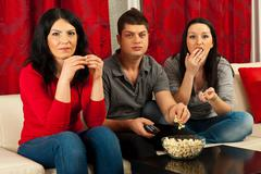 Friends eating popcorn at movie - stock photo