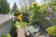 backyard with kids tree house and table with chairs. - stock photo