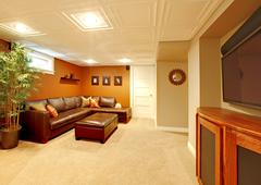 Tv media basement living room with leather sofa. Stock Photos