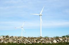 Two wind turbines by an old traditional stonewall at the swedish island oland Stock Photos
