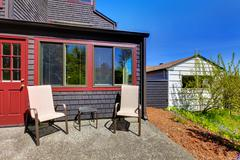 Two chairs next to red door and small black house. Stock Photos