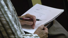 Elderly man taking notes CU hands pen paper  Stock Footage