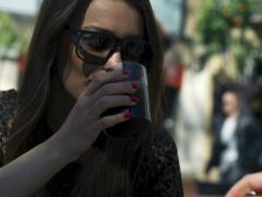 Woman talking and drinking beverage on street cafe, steadycam shot Stock Footage